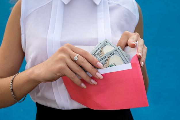 Piękna młoda biznesowa dama trzyma kopertę z dolarami
