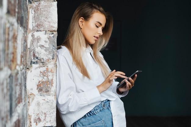 Piękna młoda biznesowa kobieta w białej koszuli stoi w pobliżu ściany z cegły