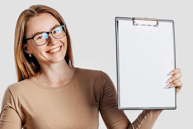 Piękna młoda biznesowa kobieta w okularach trzyma schowek z pustej przestrzeni na białym tle na szarym tle.