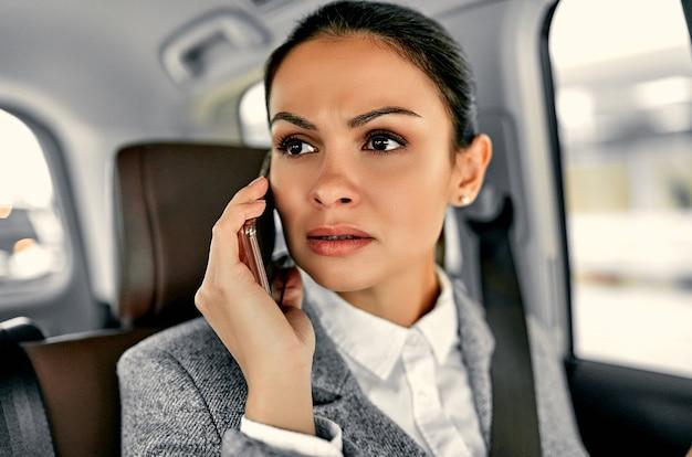 Piękna młoda biznesowa kobieta w samochodzie rozmawia przez telefon.