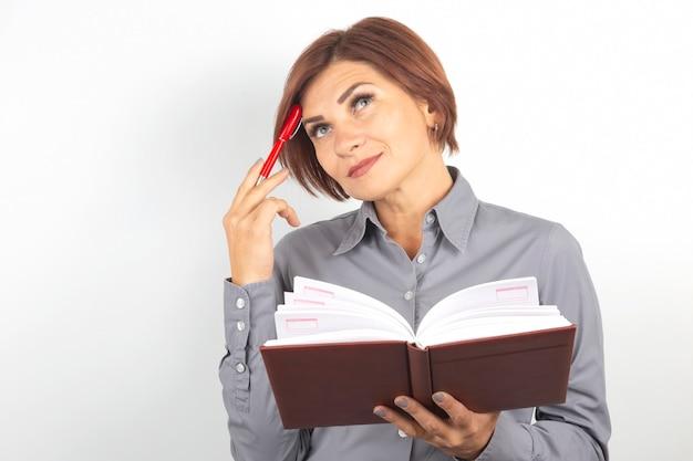 Piękna młoda biznesowa kobieta z czerwonym piórem w ręku na białym