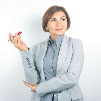 Piękna młoda biznesowa kobieta z czerwonym piórem w ręku