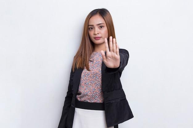 Piękna młoda biznesowa kobieta z otwartą dłonią robi znak stop z poważnym wyrazem twarzy