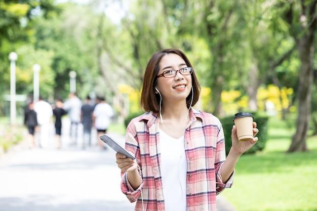 Piękna młoda bizneswoman je kawę i rano używa swojego smartfona do słuchania międzynarodowej muzyki w ogrodzie