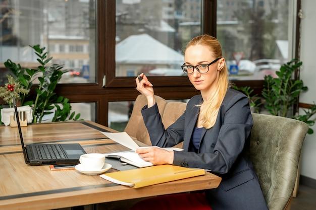 Piękna młoda bizneswoman kaukaski pracy z dokumentami w kawiarni