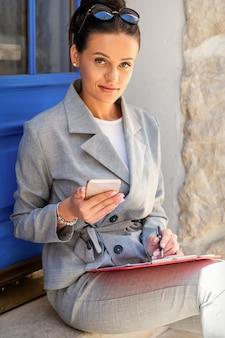 Piękna młoda bizneswoman kaukaski robienie notatek siedząc na schodach przy drzwiach
