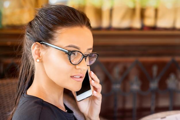 Piękna młoda bizneswoman kaukaski w okularach sprawia, że rozmowa przez telefon komórkowy w kawiarni