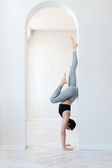 Piękna młoda blogerka fitness robi trudny handstand w jasnym pomieszczeniu. koncepcja regularnego treningu i siły woli.