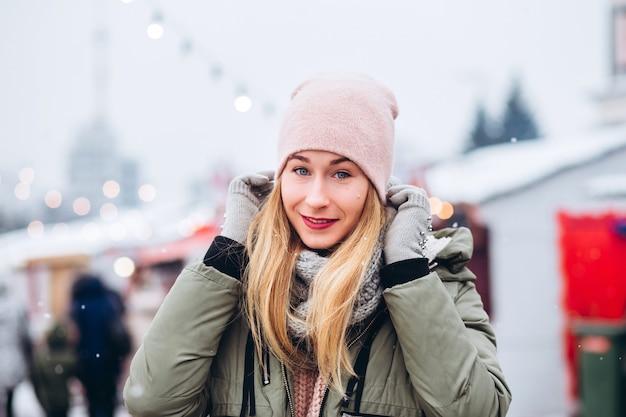Piękna młoda blond kobieta na jarmarku bożonarodzeniowym