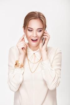 Piękna młoda blond kobieta rozmawia przez telefon i bawi się włosami. zaskoczenie i zachwyt