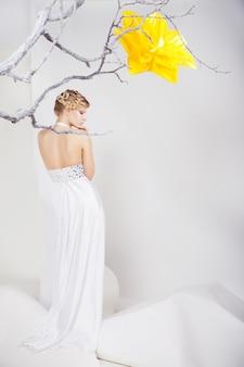 Piękna młoda blond kobieta w białej sukni z dużym żółtym kwiatem na białym tle