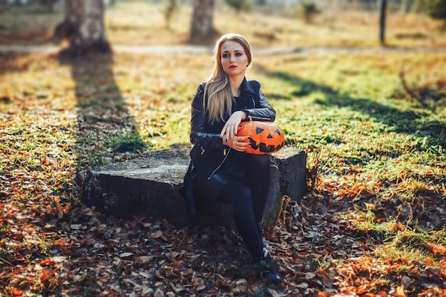Piękna młoda blond kobieta z ekstrawaganckim makijażem w czarnej skórzanej kurtce