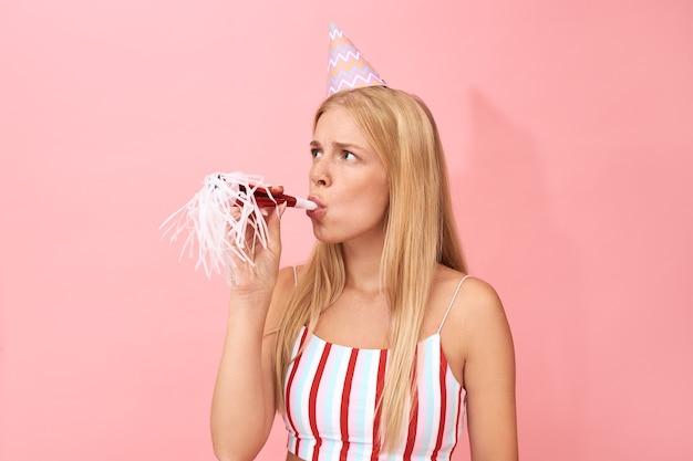 Piękna młoda blondynka bawi się na przyjęciu urodzinowym, obchodzi rocznicę z przyjaciółmi, ubrana w pasiastą górę i stożkowy kapelusz dmuchanie fajką lub gwizdkiem