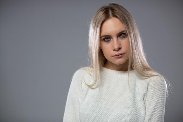 Piękna młoda blondynka gapi się w kamerę.