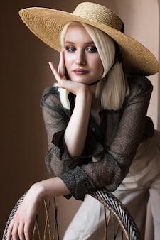 Piękna młoda blondynka model pozuje w słomkowym kapeluszu i zielonej przezroczystej bluzce