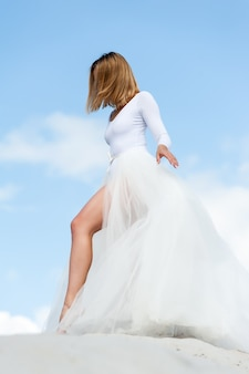 Piękna młoda blondynka panna młoda w białej sukni plenerowej