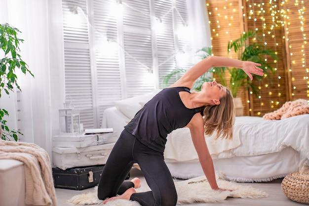 Piękna młoda blondynka, rozciągając mięśnie ramion i pleców, wykonuje ćwiczenia gimnastyczne w domu