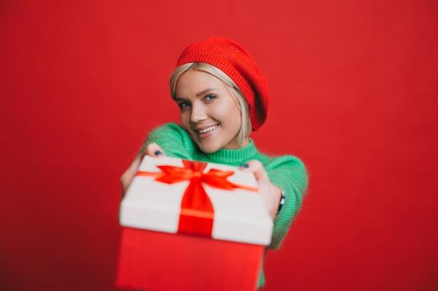 Piękna młoda blondynka ubrana na zielono patrząc na kamery, uśmiechając się, dając czerwone pudełko na białym tle na czerwonej ścianie studio.