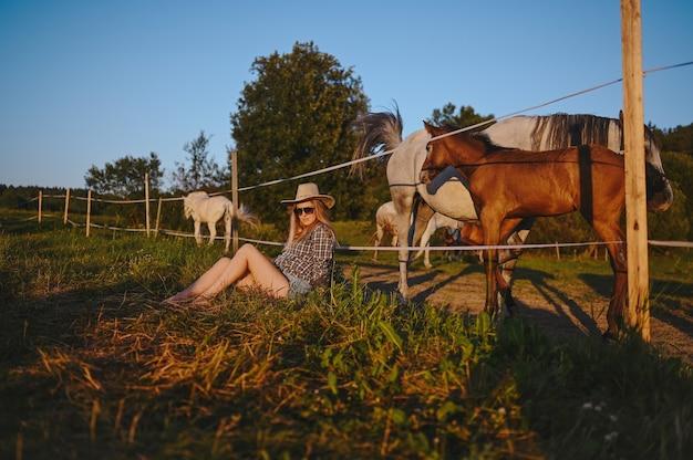 Piękna młoda blondynka ubrana w stylu safari w kapeluszu i koszuli w kratę pozowanie z rasami!