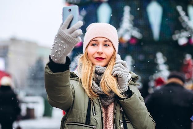 Piękna młoda blondynka uśmiecha się do telefonu do zdjęcia na jarmark bożonarodzeniowy