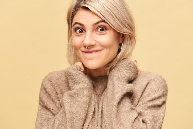 Piękna młoda blondynka w ciepłym kaszmirowym swetrze, trzymając się za ręce na twarzy i przewidując tajemniczy wyraz twarzy. enigmatyczna dziewczyna wyrażająca prawdziwą, autentyczną reakcję