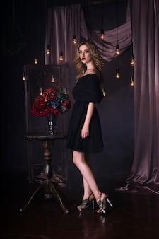Piękna młoda blondynka w czarnej sukni z makijażem halloween i krwawą sztuką twarzy