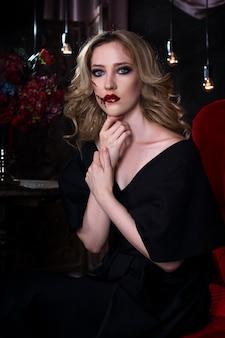 Piękna młoda blondynka w czerwonej sukience z halloween makijaż i krwawą twarz sztuki, wnętrza vintage
