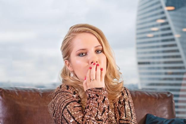 Piękna młoda blondynka w modnej sukience pozuje na skórzanej sofie z lampką szampana na tle panoramicznego okna z widokiem na wieżowce i duże miasto