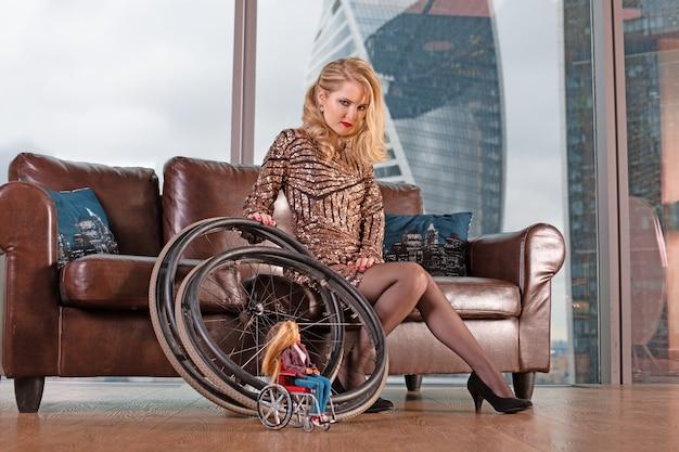 Piękna młoda blondynka w modnej sukience z niepełnosprawnością pozuje na skórzanej sofie na tle panoramicznego okna z widokiem na wieżowce i duże miasto