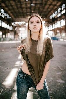 Piękna młoda blondynka w pustej zielonej koszulce