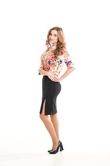 Piękna młoda blondynka w stroju biurowym na białym tle, w bluzce z kwiatami, czarną spódnicą i butami na obcasach w studio, pozuje do aparatu, modny luksusowy makijaż