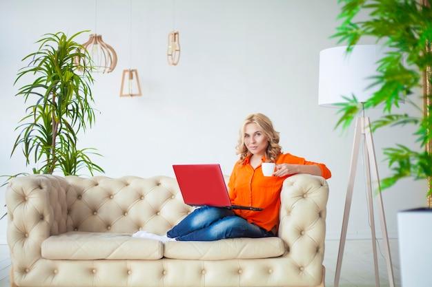 Piękna młoda blondynka w ubranie pracuje z laptopem na kanapie w domu