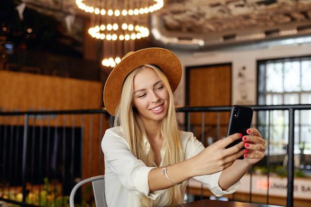 Piękna młoda blondynka z długimi włosami w kapeluszu i białej koszuli, pozuje nad wnętrzem kawiarni, uśmiechając się szeroko podczas robienia selfie ze swoim smartfonem