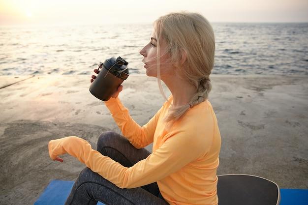 Piękna młoda blondynka z przypadkową fryzurą, ubrana w pomarańczowy top z długim rękawem i ciemne legginsy, siedząca nad brzegiem morza wczesnym rankiem, pijąca białko przed treningiem