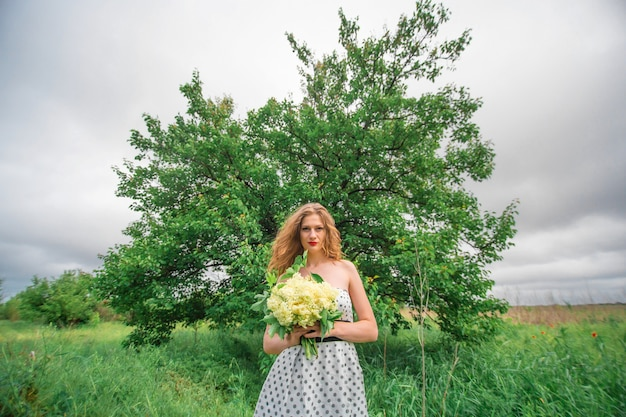 Piękna młoda blondynka zebrała bukiet polnych kwiatów. zapraszamy na spacer w ciepły letni dzień.
