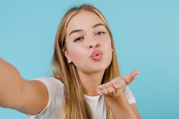 Piękna młoda blondynki dziewczyna robi selfie odizolowywającemu nad błękitem
