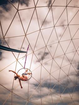 Piękna młoda blondynki dziewczyna w treningu siłowni powietrznej na wystawę pokazową i stalową konstrukcję i chmury