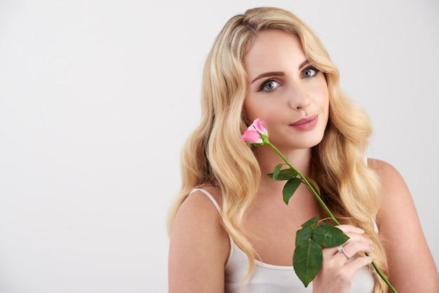 Piękna młoda blondynki kaukaska kobieta w camisole wierzchołku pozuje z menchii różą