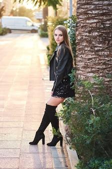 Piękna młoda blondynki kobieta jest ubranym stylową czarną kurtkę