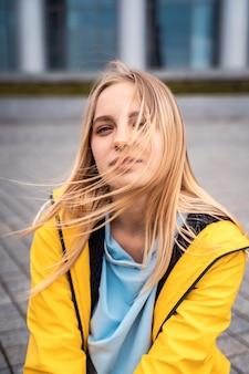 Piękna młoda blondynki kobieta na ulicie, pozuje z wiatrem w jej włosy