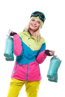 Piękna młoda blondynki kobieta w kolorowym śnieżnym żakiecie trzyma śnieżne buty