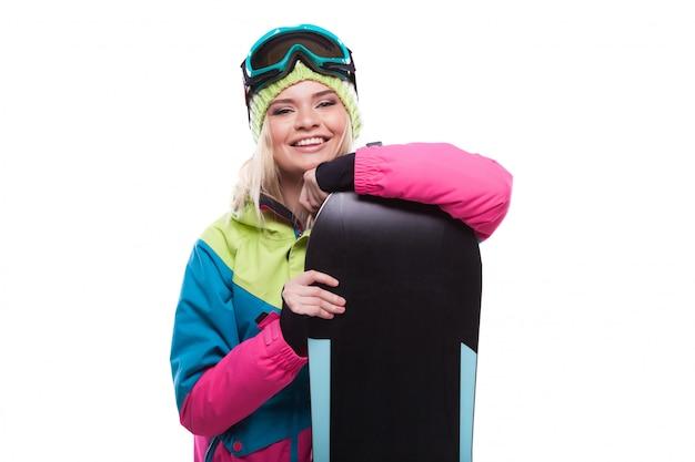 Piękna młoda blondynki kobieta w kolorowym śnieżnym żakiecie trzyma snowboard