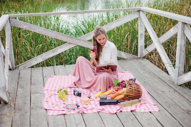 Piękna młoda blondynki kobieta w roczników retro ubraniach ma pinkin na drewnianym molu samotnie. piknik w stylu francuskim na świeżym powietrzu