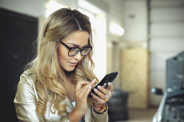 Piękna młoda blondynki kobieta w szkłach dzwoni na telefonie i auto mechaniku dla auto naprawy