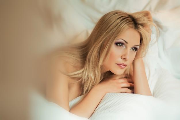 Piękna młoda blondynki kobieta wygrzewa się w białej sypialni w ranku