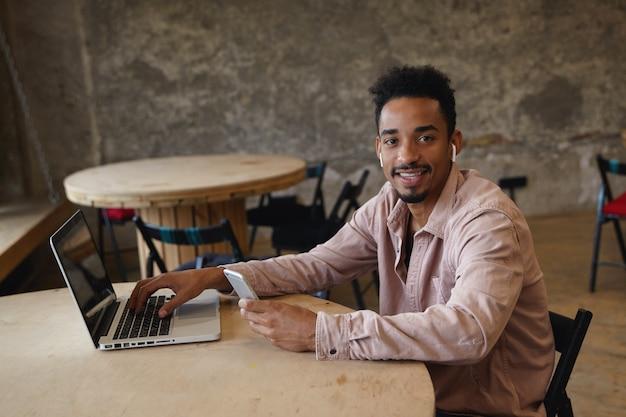Piękna młoda brodata freelancer o ciemnej skórze podczas przerwy obiadowej w miejskiej kawiarni, siedząca przy stole z laptopem i trzymająca rękę na klawiaturze, trzymając telefon komórkowy i wesoło patrząc na aparat