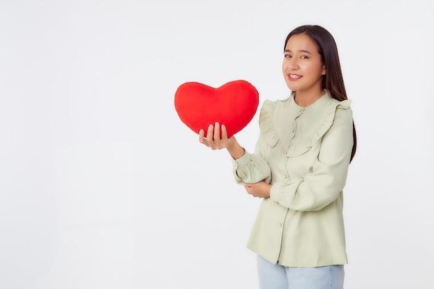 Piękna młoda brunetka azji kobieta ubrana w zieloną koszulę stojącą trzymać poduszkę w kształcie czerwonego serca w jasnoszarym na białym tle powierzchni studia