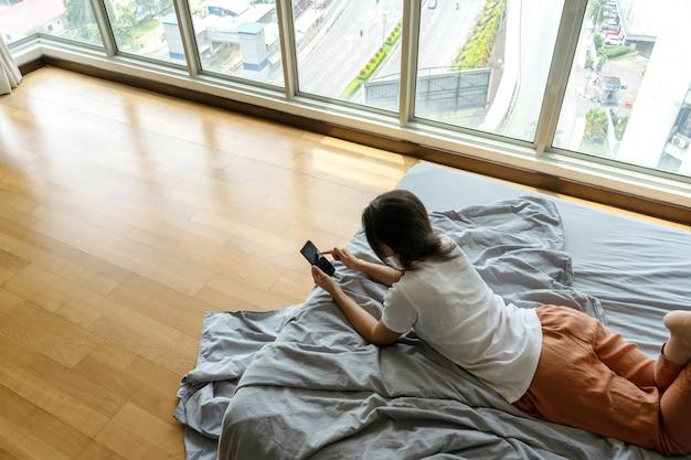 Piękna młoda brunetka dziewczyna pisze sms-em przez telefon, leżąc na łóżku przy panoramicznym oknie z pięknym widokiem z wysokiej podłogi.