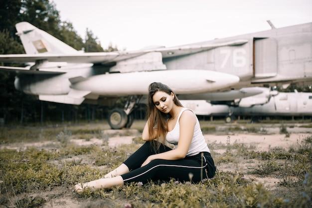 Piękna młoda brunetka dziewczyna stoi na powierzchni starych samolotów wojskowych. dziewczyna w białej koszuli i czarnych spodniach w naturze.