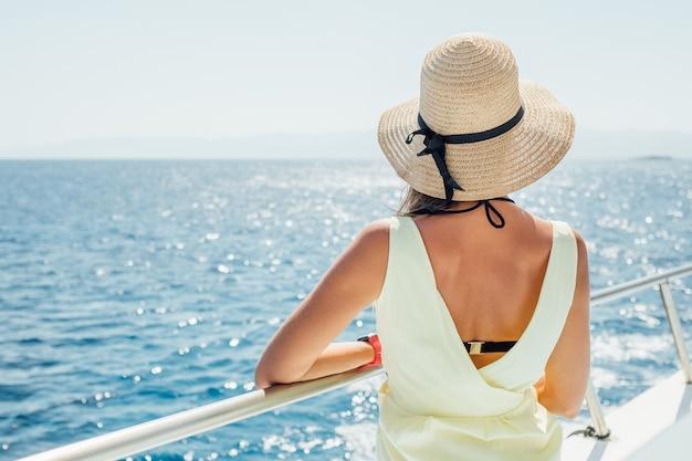 Piękna młoda brunetka dziewczyna w żółtej sukience. letnia wycieczka na jachcie po morzu lub oceanie